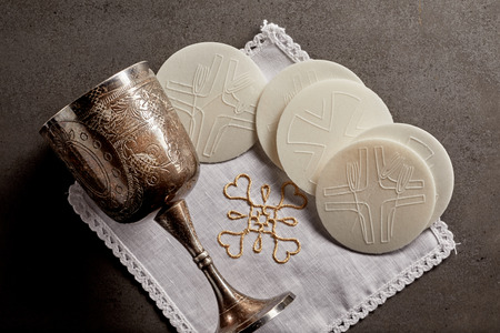 Silver chalice cup and Sacramental bread, or Hosties, symbolising the blood and body of the resurrected Christ for the Communion Service Zdjęcie Seryjne