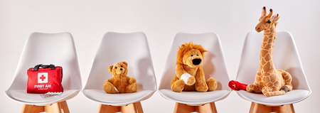 Three cute stuffed animal toys on chairs in the waiting room of a modern hospital or health center for children