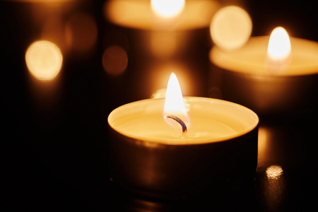 Spiritual concept of lighted tealight candles in close up view
