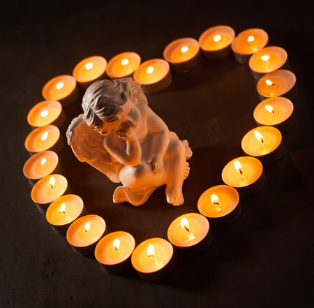 Little angel in a heart shaped frame of burning candles over a dark background conceptual of the loss of a loved one, sorrow and remembrance Banco de Imagens