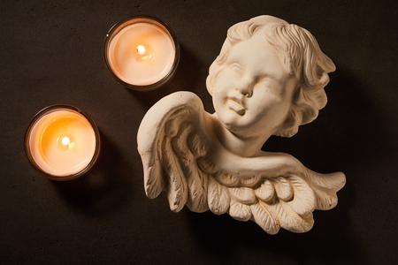 어두운 배경 위에 촛불을 굽기와 함께 천사의 천사 영성, 슬픔, 사별과 애도의 개념
