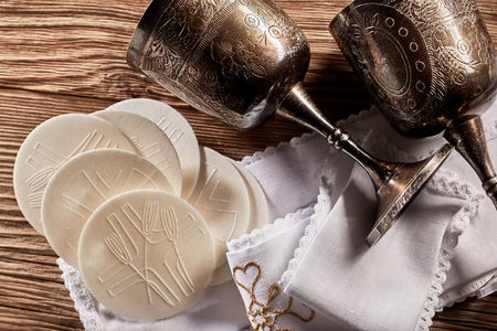 Sacramental Hosties with silver chalice cups for the red wine symbolising the body and blood of the resurrected Christ for the Holy Communion church service Фото со стока - 93874860