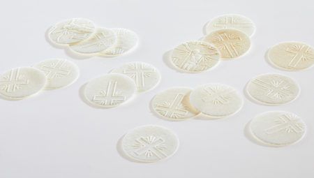 Scattered sacramental Hosties on a white background symbolic of the body of the resurrected Christ used in Holy Communion