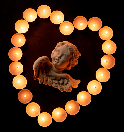 High-angle close-up view of a vintage angel figurine in a heart shape made of burning prayer candles on dark background for copy space