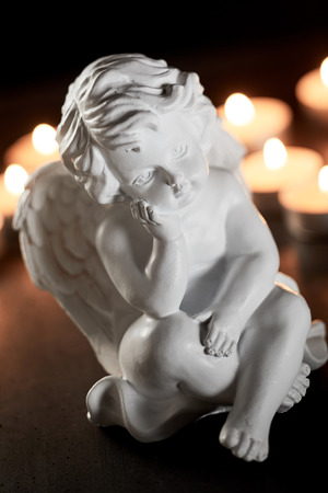 Inspirational close-up of a vintage white angel figurine against burning prayer candles for commemoration