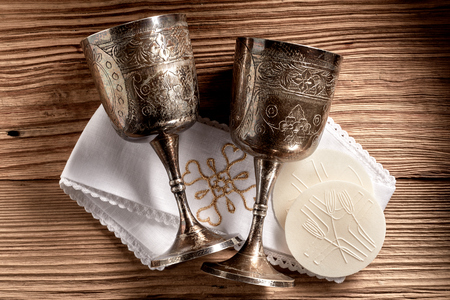 Hostie wafers with silver chalice cups and cloth ready for the Holy Communion service in a church on rustic wood background