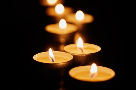 Nature morte d'inspiration religieuse avec des bougies votives allumées pour des prières ou une commémoration sur un fond sombre pour l'espace de copie