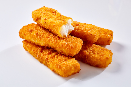 Tasty crispy deep fried fish fingers lying against white background