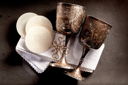 Consecrated Sacramental bread or Hosties and silver chalice cups for the wine symbolising the body and blood of the resurrected Christ