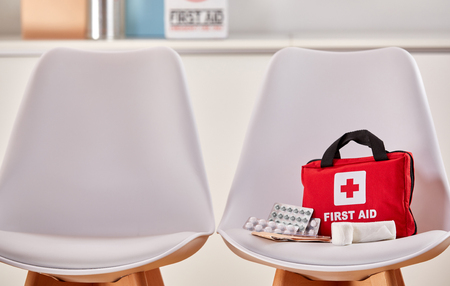 Trousse de secours comme concept de soins de santé à côté d'une chaise vide dans la salle d'attente d'un hôpital ou d'un centre médical Banque d'images - 93912648