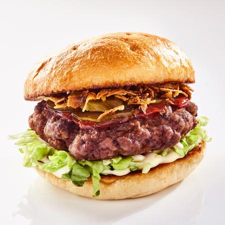 메뉴 또는 광고에 흰색 위에 구운 또는 구운 피 각 질의 롤빵에 양상추의 침대에 선명 하 게 딱딱 소리와 돼지 고기 배꼽 햄버거