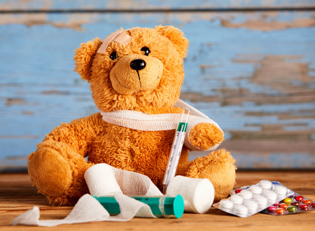 Cute stuffed teddy with a broken arm in a sling alongside rolls of clean bandages, syringe, thermometer and tablets in a concept of paediatric healthcare