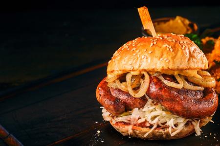 복사 공간이 어두운 배경 위에 참깨 롤빵에 매운 전통적인 독일어 소 세 지 먹은 햄버거