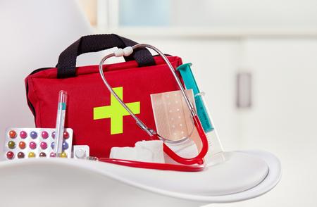 Nahaufnahme einer Erste-Hilfe-Ausrüstung nahe bei bunten Pillen, Spritze, Stethoskop und sterilen Verbänden auf einem weißen Stuhl in einem Gesundheitszentrum