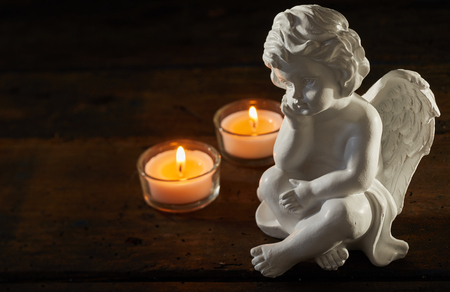 Angel figurine with burning candles on a dark wood background with copy space conceptual of sorrow and bereavement Banco de Imagens