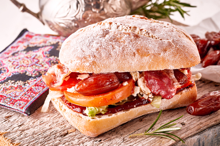 Delicious date and feta cheese sandwich on a crusty bun with tomato, ketchup and rosemary Foto de archivo