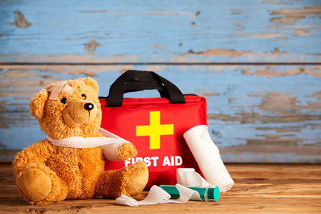 Paediatric healthcare concept with a little teddy bear with its arm in a sling alongside a first aid kit and bandages on rustic wood Standard-Bild