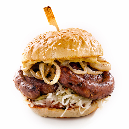 Grilled spicy bratwurst burger on a sesame bun with fried onion rings over a white background for advertising Stock Photo