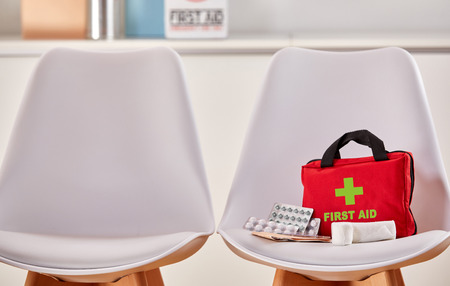 First aid kit as concept for health care next to an empty chair in the waiting room of a hospital or a medical center