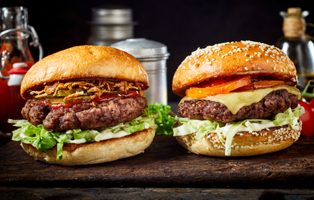 Hambúrgueres saborosos de carne fresca com salada e queijo, servido na tábua de madeira Foto de archivo