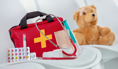 Close-up of a first aid kit next to a stethoscope, colorful pills, a syringe and sterile bandages on a chair in the waiting room of a medical center
