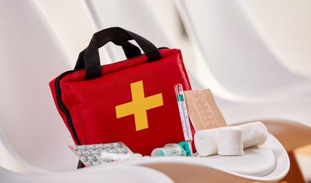 Close-up de um kit de primeiros socorros com bandagens estéreis, pílulas e seringas para emergência na sala de espera de um hospital ou centro de saúde