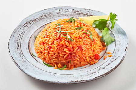 Serving of healthy nutritious Greek tomato pilaf with long grained rice and fresh coriander on an old rustic pottery plate Stock Photo