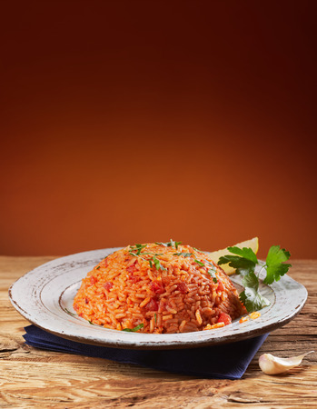 Plate of tasty seasoned Greek tomato rice, pilaff or dormatrizo, garnished with coriander with a clove of garlic to the side and copy space above