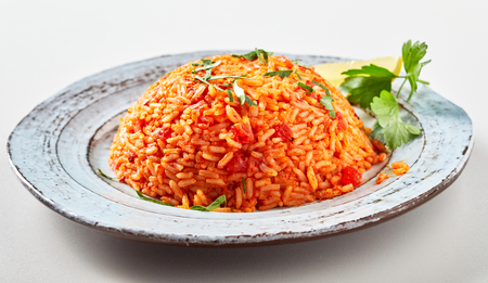Traditional greek tomato rice, domatoriza or pilaf, and coriander on a rustic plate in a low angle side view served in a neat mound