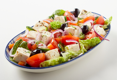Greek salad with cubed feta cheese and black olives on a bed of fresh lettuce, tomato, onion and cucumber served on an oval plate Reklamní fotografie