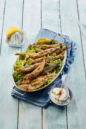 Platter of fried battered sardines with a refreshing raita yogurt sauce and lemon on the side served on a blue napkin and matching wooden table in a high angle view