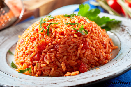 Tasty Greek domatorizo or tomato rice garnished with chopped fresh coriander in a close up side view on a plate Stock Photo