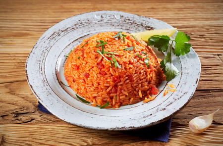 Healthy fresh long grain rice tomato pilaf, or Greek domatorizo, seasoned with fresh coriander and garlic on a wooden table