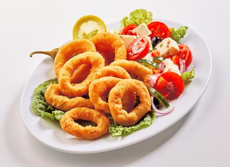 Sabroso almuerzo de mariscos con aros de calamar rebozados fritos y ensalada griega con queso feta y aceitunas servidos en una bandeja ovalada en blanco Foto de archivo - 95524545