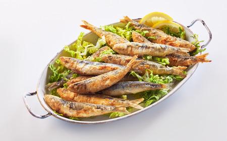 Healthy regional Greek seafood meal of crisp fried sardines in batter on fresh lettuce Stock Photo