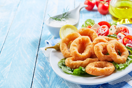 Delicious seafood meal of deep-fried golden squid rings and Greek salad on an oval platter with copy space on blue wood Foto de archivo