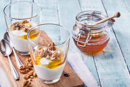 Two tasty natural desserts with Greek yogurt, raw fresh walnuts and a topping of honey served in individual glasses Stock Photo