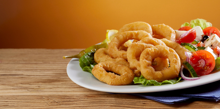 Golden fried calamari rings with fresh Greek salad served on a platter on a wooden counter with copy space in banner format