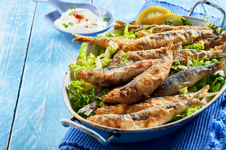 Healthy Mediterranean or Greek appetizer of fried sardines in batter on a bed of fresh lettuce served in a vintage dish over a blue wood background with copy space