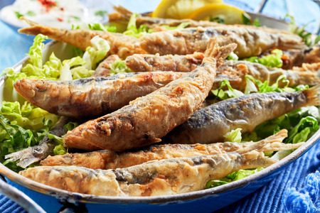 Traditional Greek crispy fried sardines in batter on a bed of fresh green lettuce in a close up view Zdjęcie Seryjne