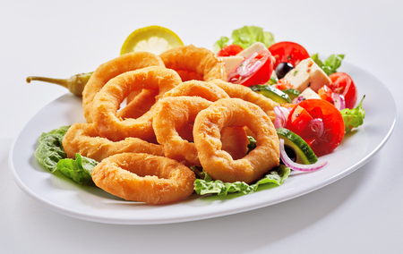 Healthy seafood appetizer with deep-fried golden rings of squid and a fresh Greek salad served on an oval plate over white Foto de archivo