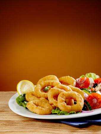Golden crispy fried calamari or squid rings in batter served with a healthy fresh salad to the side in a close up vertical view with copy space above