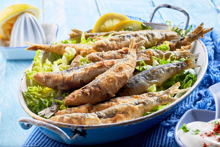 Crispy batter fried Greek sardines, pilchards or anchovies in an old vintage oval dish dressed with lemon and served with raita in a close up view