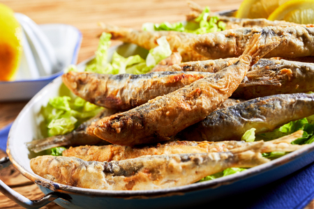 Plate of crispy fried sardines, pilchards or anchovies, a traditional Mediterranean dish, in a close up view with selective focus to one fish