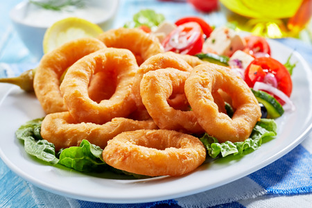 Crisp fried golden squid rings with a fresh Greek salad in a close up view on a plate Standard-Bild