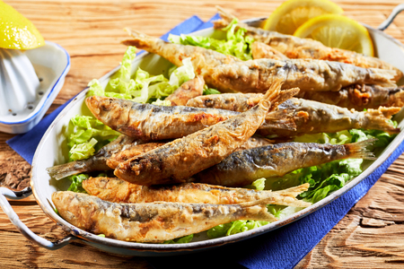 Dish of battered fried sardines, pilchards or anchovies on a bed of fresh lettuce for a healthy Greek regional meal Archivio Fotografico