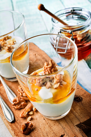 Thick creamy natural Greek yogurt with a topping of honey and walnuts served in a glass on a wooden board with ingredients alongside Stock Photo