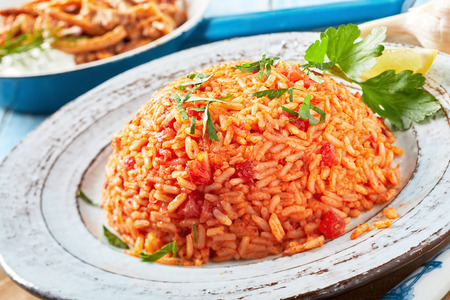 Healthy nutritious plate of Greek tomato rice or pilaf topped with fresh chopped coriander and served on a rustic earthenware plate Stock Photo