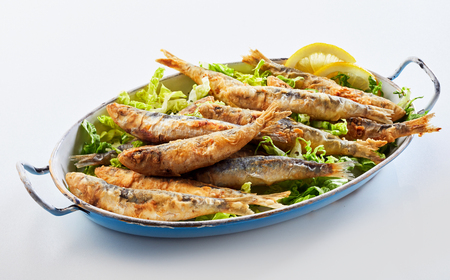 Old vintage dish with fried sardines, pilchards or anchovies in batter on a bed of lettuce for a traditional Greek meal
