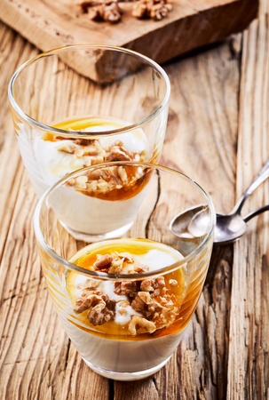 Healthy natural Greek yogurt dessert topped with fresh walnuts and honey as a sweetener served in two glasses on rustic wood